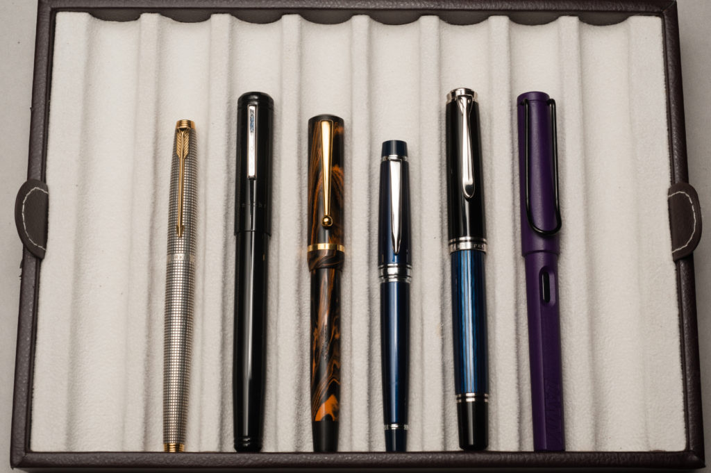Closed pens from left to right: Parker 75, Franklin-Christoph Model 20, Edison Beaumont, Pilot Stargazer, Pelikan M805, and Lamy Safari