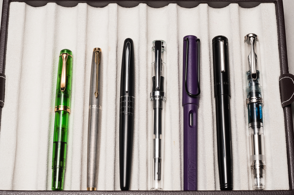 Closed pens from left to right: Pelikan M200, Parker 75, Pilot Metropolitan, *Nemosine Singularity*, Lamy Safari, Franklin-Christoph Model 20, and Pelikan M805